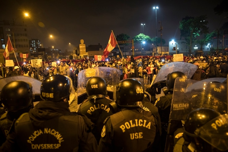Policemen stand guard as people demonstrate the refusal to recognize Peru's new government, in Lima, Saturday, Nov. 14, 2020…