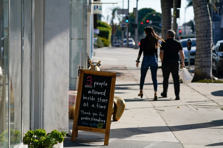 A sign restricting the number of customers stands outside of a shop Wednesday, Nov. 18, 2020, in the West Hollywood area of Los…