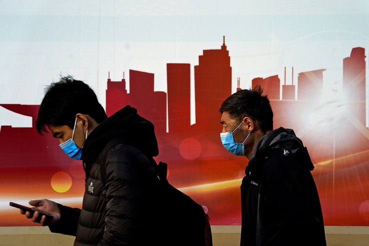 People wearing face masks to help curb the spread of the coronavirus walk by a moral depicting China's skyscrapers along a…
