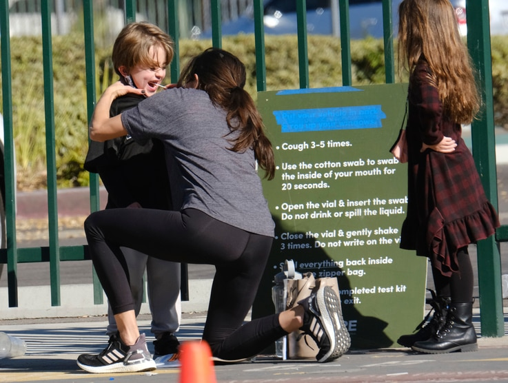 A woman swabs a child's cheek for a COVID-19 test at a testing site in the North Hollywood section of Los Angeles on Saturday,…