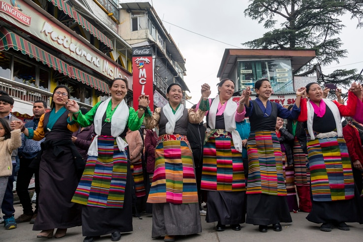 Exile Tibetans perform a traditional communal dance in the town square to celebrate the third day of the Tibetan New Year or…