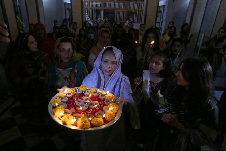 Hindu women attend a ceremony to celebrate Diwali, the festival of lights, at Swami Narayan temple in Karachi, Pakistan,…