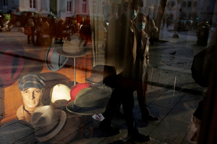 A couple wearing face masks are reflected on the window of a hat shop in downtown Lisbon, Wednesday, Dec. 2, 2020. (AP Photo…