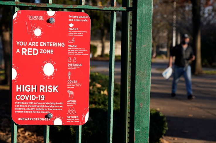 A sign at the entrance to a park warns pedestrians about increased risk for the coronavirus in the Ironbound section of Newark,…
