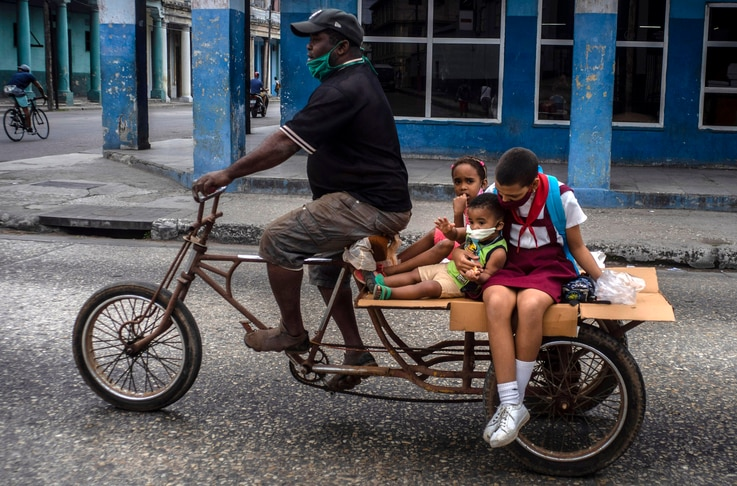 A man transports children on his tricycle, in Havana, Cuba, Friday, Jan 8, 2021, amid the new coronavirus pandemic. (AP Photo…
