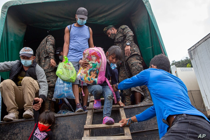 A Honduran migrant child is helped off a Guatemalan army truck after being returned to El Florido, Guatemala, one of the border…