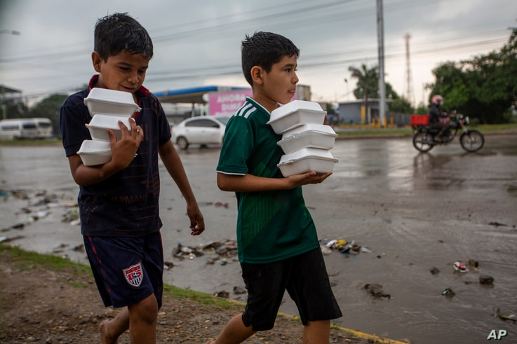 Youths carry donated hot meals back to their tents alongside a highway where they live with others after last year's hurricanes…