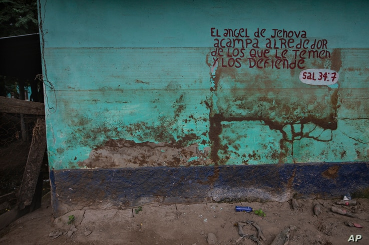 Stains left by mud and water from last year's hurricanes Eta and Iota mark a wall decorated by a Bible passage in the Saviñon…