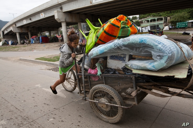 Floria Sarai Calix pushes her belongings in hopes of finding a safer area to camp out with her son after losing their home in…