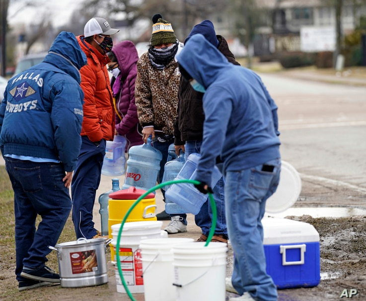 People wait in line to fill containers with water from a park spigot Thursday, Feb. 18, 2021, in Houston. Houston and several…