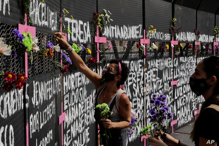 Women place flowers on a perimeter fence set up in front of the National Palace in preparation for the upcoming International…