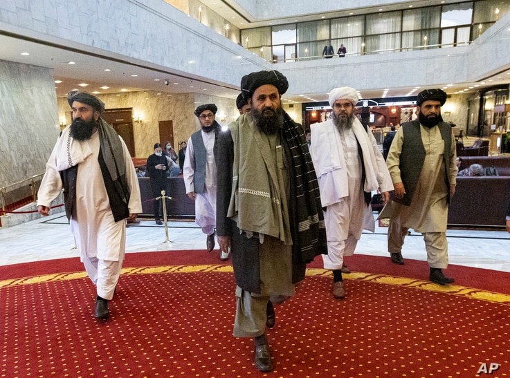 Taliban co-founder Mullah Abdul Ghani Baradar, center, arrives with other members of the Taliban delegation for an…