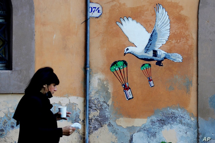 A woman walks past a mural depicting a white dove parachuting COVID-19 vaccine vials, posted near the Italian Health Ministry…