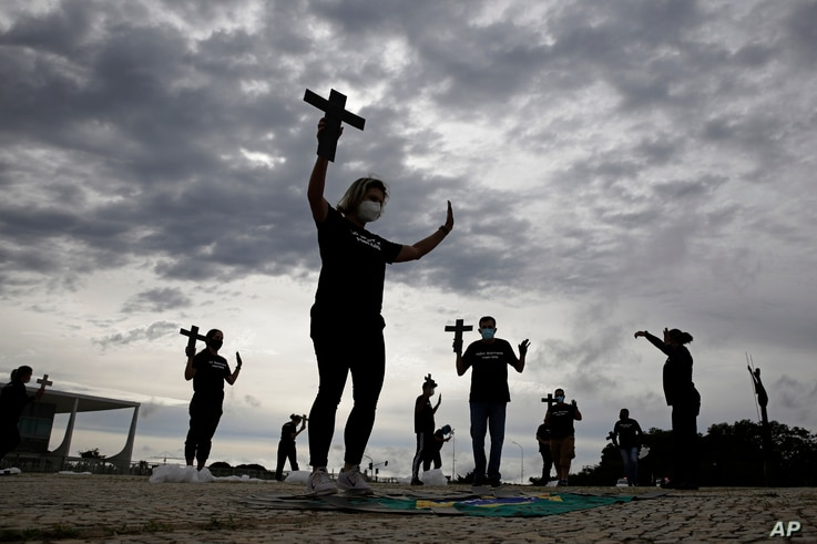 Protesters hold crosses marking the milestone of 400,000 COVID-19-related deaths in Brazil.