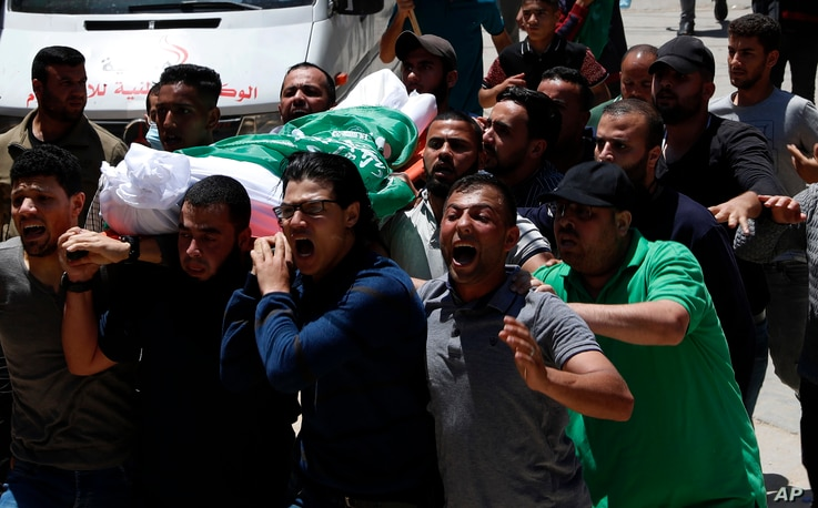 Mourners chant Islamic slogans while carrying the body of Awad Abu Selmiya, during a funeral of thirteen Hamas militants…