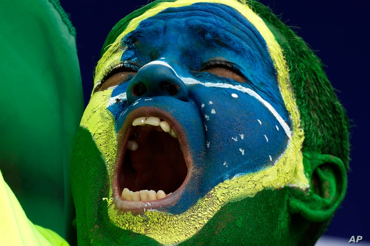 A protester with a Brazilian flag painted on his face raises slogans during a caravan in support of President Jair Bolzano