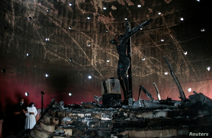 A priest and a nun pray in front of an image of Sangre de Cristo after it was destroyed by a fire at the Metropolitan Cathedral in Managua