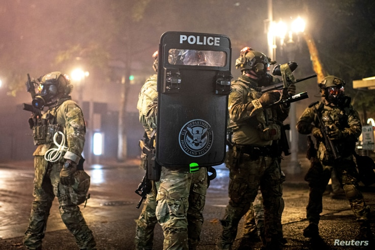 Federal law enforcement officers guard a courthouse during unrest that followed the grand jury decision in Portland