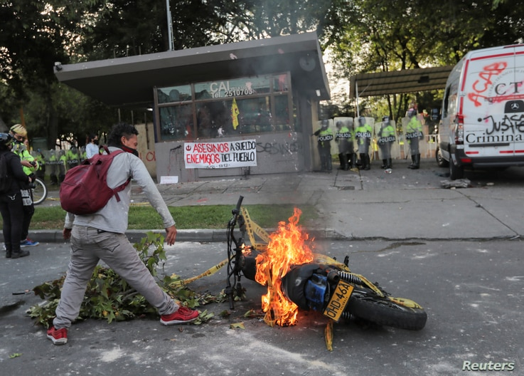 A demonstrator stands near a burning motorcycle outside a police station after a man, who was detained for violating social distancing rules, died from being repeatedly shocked with a stun gun by officers, according to authorities, in Bogota