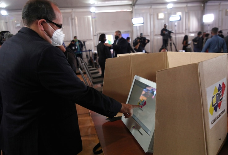 Man simulates his vote as the Venezuela's National Electoral Council presents the technology platform for the upcoming parliamentary elections in Caracas