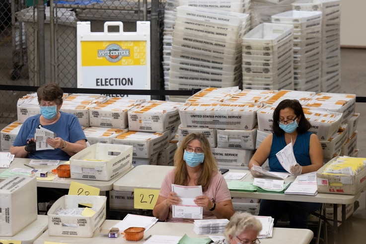 Election workers sort through some of the thousands of mail-in ballots at the Orange County Registrar of Voters in Santa Ana, California