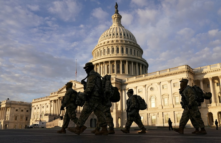 FILE PHOTO: National Guard members walk in front of the U.S. Capitol after the House voted to impeach U.S. President Donald Trump in Washington