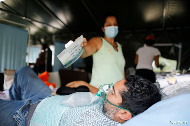 A woman shows a mask packaging to a patient who is suffering from the coronavirus disease (COVID-19) as he wears an oxygen mask, at the shock and trauma medical tent in the Poliedro de Caracas