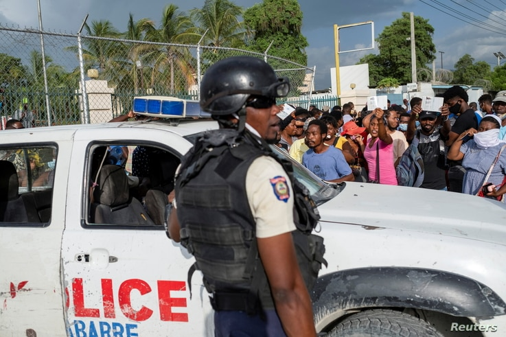 Haitian National Policemen guard the entrance to the U.S. Embassy as people gather to ask for asylum following the assassination of President Jovenel Moise