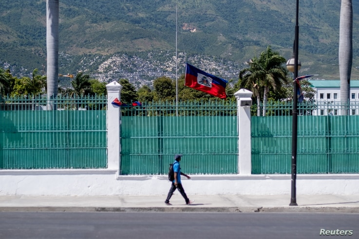 A man walks past in front of where the Haitian Presidential Palace used to be with the Haitian national flag at half-mast, in Port-au-Prince